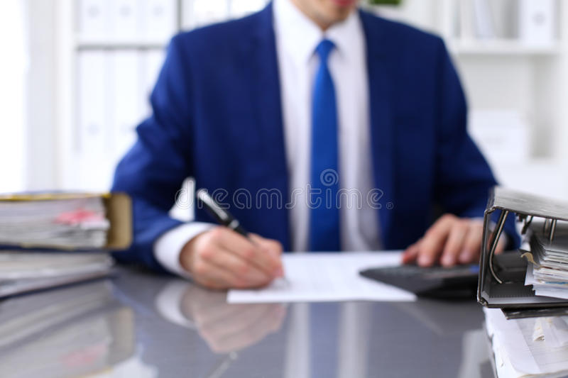 Binders with papers are waiting to be processed with businessman back in blur. Accounting planning budget, audit. Insurance and business concept royalty free stock photos