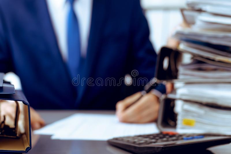 Binders with papers waiting to be processed with businessman or bookkeeper back in blur. Accounting planning budget. Binders with papers are waiting to be royalty free stock photography