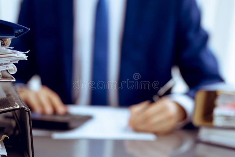 Binders with papers waiting to be processed with businessman or bookkeeper back in blur. Accounting planning budget. Binders with papers are waiting to be royalty free stock photos