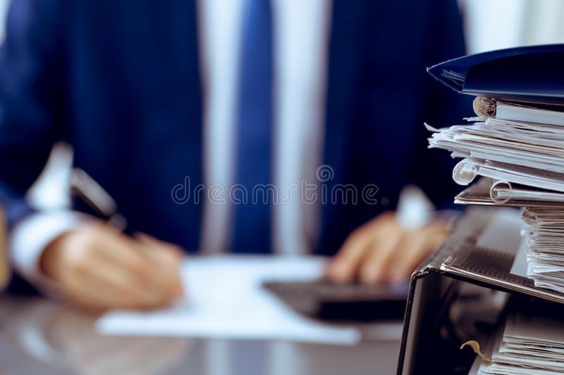 Binders with papers waiting to be processed with businessman or bookkeeper back in blur. Accounting planning budget. Binders with papers are waiting to be royalty free stock image
