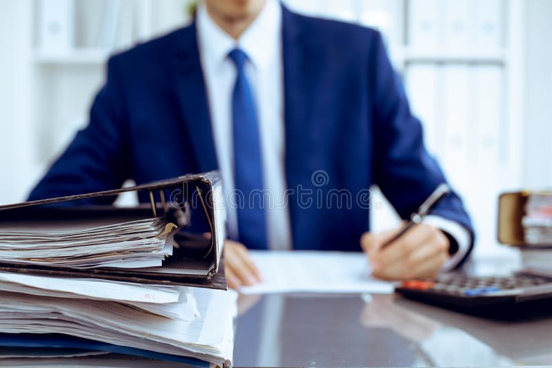 Binders with papers waiting to be processed with businessman or bookkeeper back in blur. Accounting planning budget. Binders with papers are waiting to be stock images