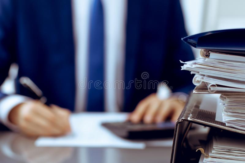 Binders with papers waiting to be processed with businessman or bookkeeper back in blur. Accounting planning budget. Binders with papers are waiting to be stock photo