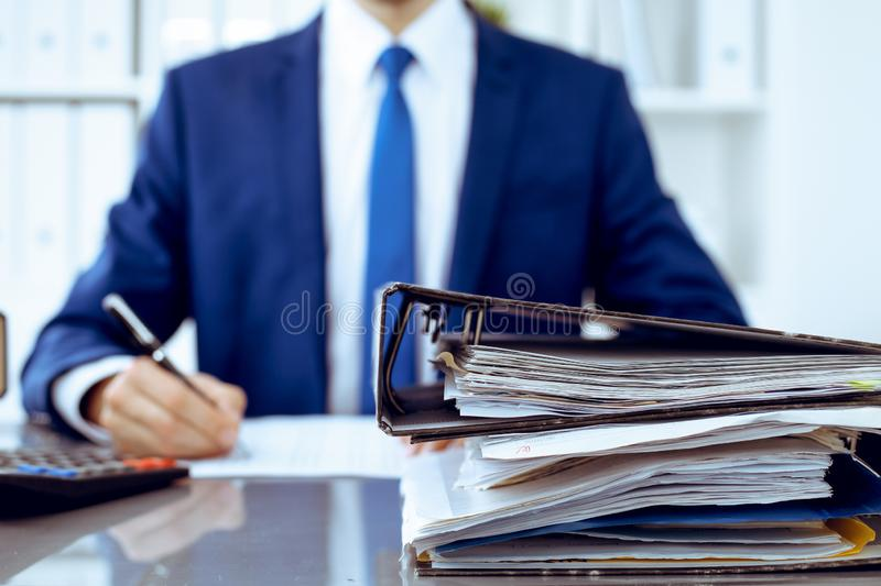 Binders with papers waiting to be processed with businessman or bookkeeper back in blur. Accounting planning budget. Binders with papers are waiting to be stock photography