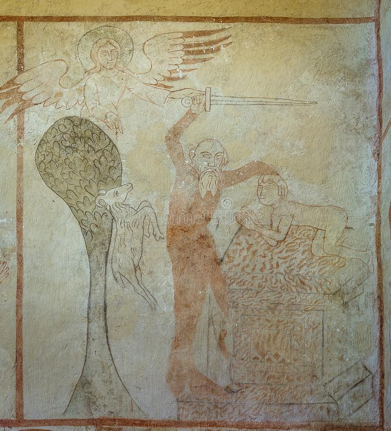 The binding of Isaac. God asks Abraham to sacrifice his son, Isaac but is prevented by an angel, a 500 years old gotic fresco in Tirsted church, Denmark, April royalty free stock image