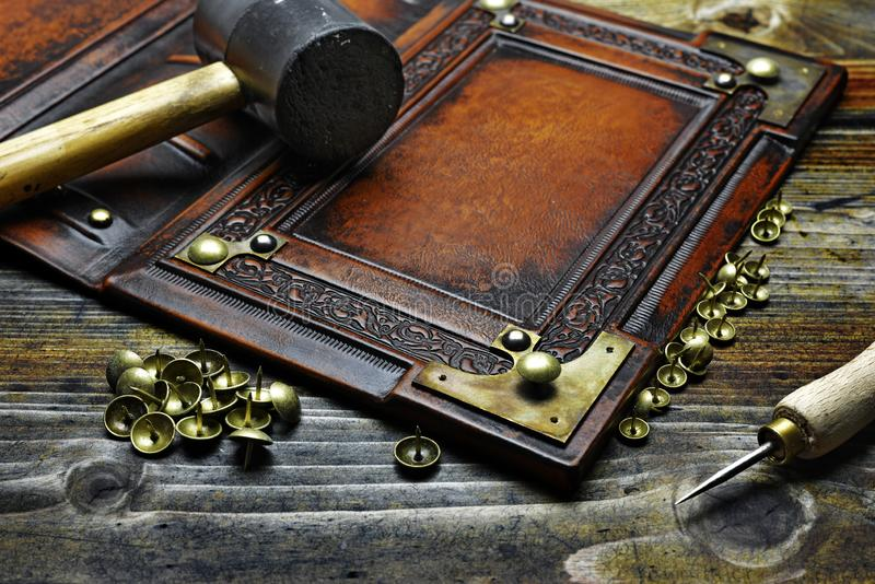 Binding the leather book with recessed central part, deeply embossed frame and brass metal corners.  royalty free stock photography