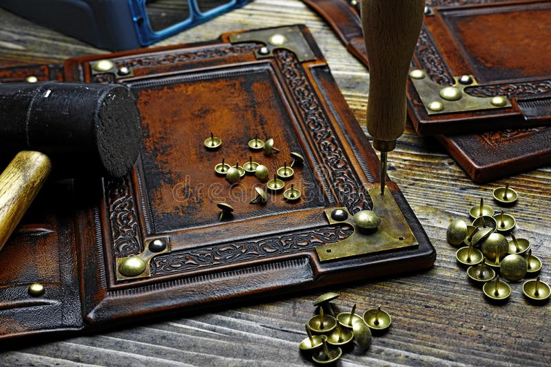 Binding the leather book with recessed central part, deeply embossed frame and brass metal corners.  stock photos