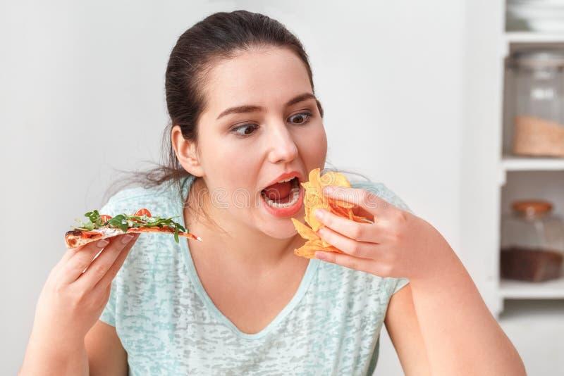 Binge Eetsen Chubby meisje dat aan keukentafel zit en pizza eet en chips die dicht bij elkaar zitten stock afbeeldingen