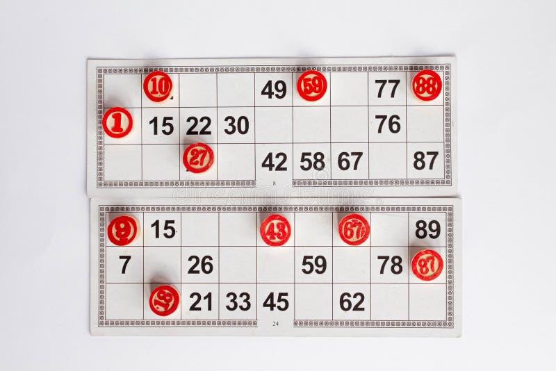 Bingo eller lottolek Träkaggar av lottot på kort Kort och chiper för att spela bingo på en vit tabell arkivbilder