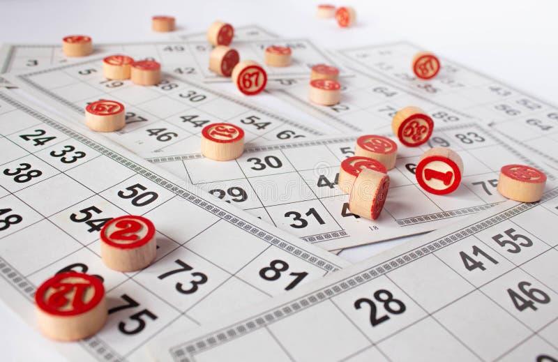 Bingo eller lottolek Tr?kaggar av lottot p? kort Kort och chiper f?r att spela bingo p? en vit tabell arkivbild