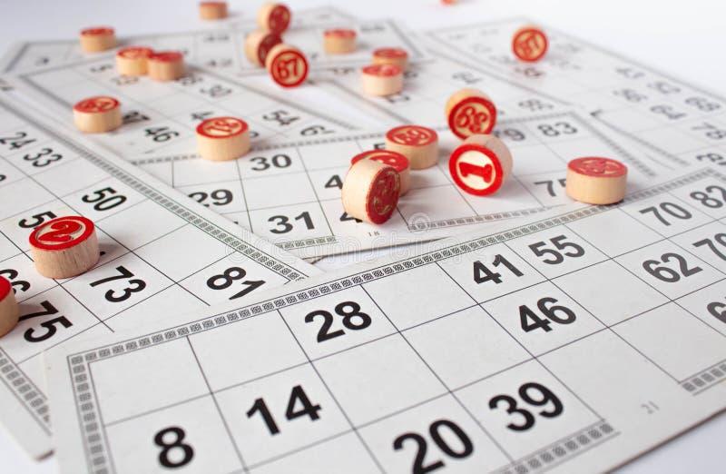 Bingo eller lottolek Tr?kaggar av lottot p? kort Kort och chiper f?r att spela bingo p? en vit tabell royaltyfria foton