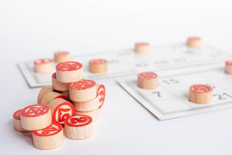 Bingo eller lottolek Tr?kaggar av lottot p? kort Kort och chiper f?r att spela bingo p? en vit tabell arkivfoto