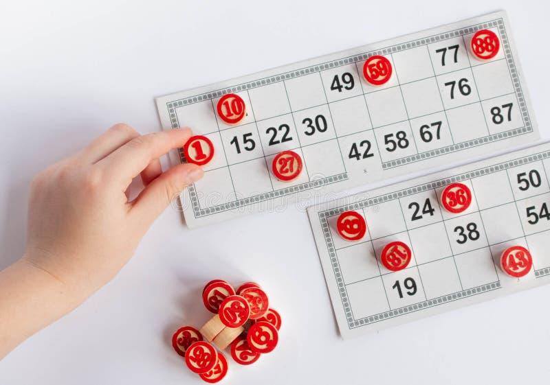 Bingo ou jogo do loto Barris de madeira do loto em cart?es Cart?es e microplaquetas para jogar o bingo em uma tabela branca imagens de stock royalty free