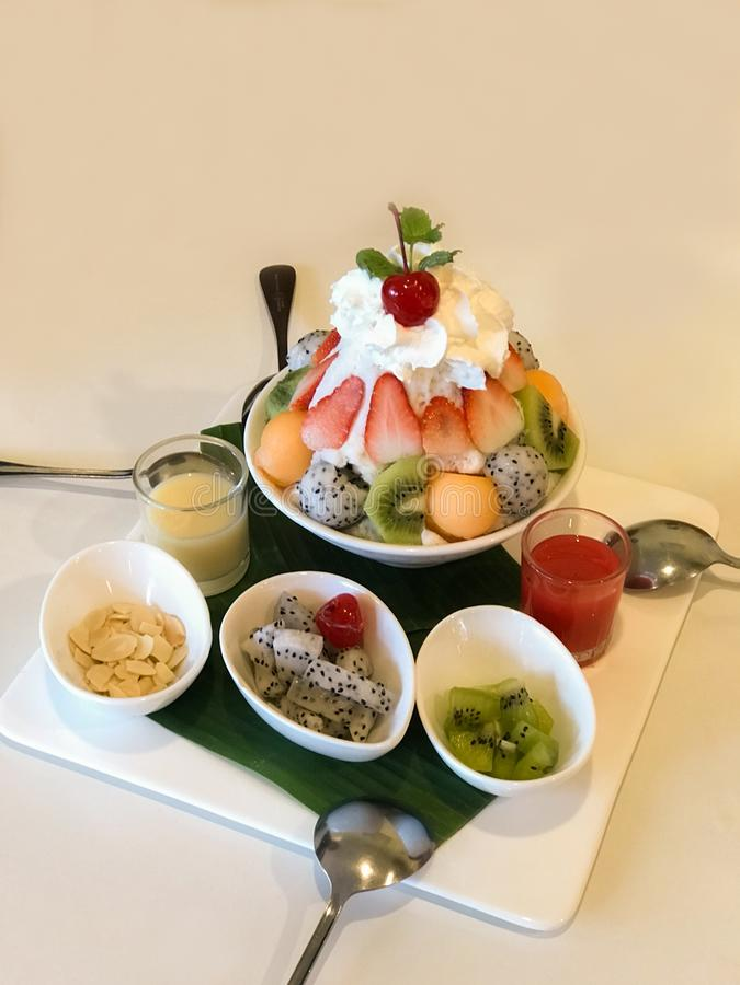 Bingsu, popular Korean shaved ice dessert with sweet topping chopped fruit and condensed milk royalty free stock image