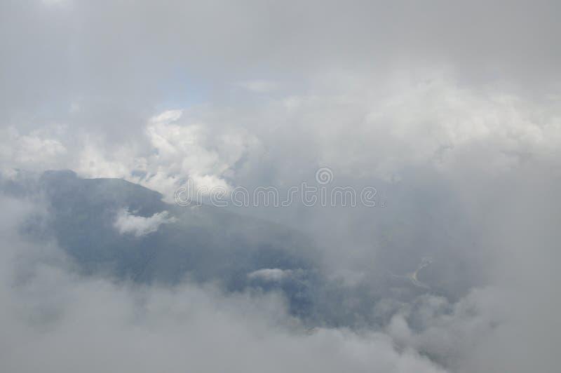 Binnen de wolken Fantastische achtergrond met wolken over bergpieken stock afbeelding