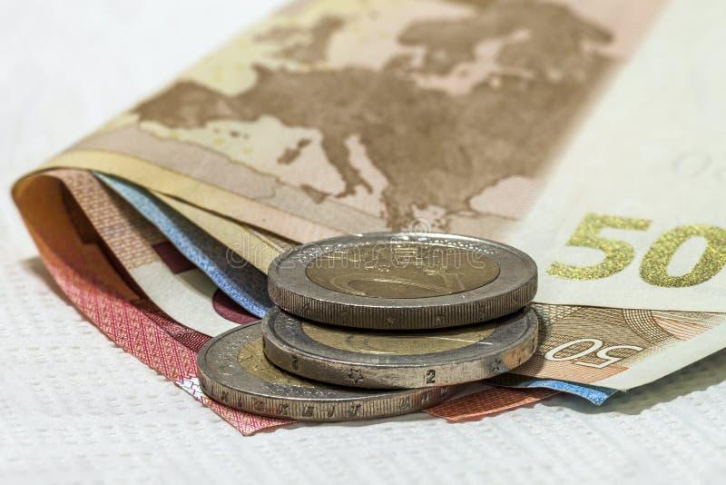 Binnen differen de de geld euro muntstukken en bankbiljetten die op elkaar worden gestapeld stock afbeeldingen