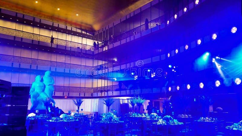 Binnen een feestelijke banketzaal, met blauwe en oranje verlichting, een marmeren standbeeld, vleklichten, en een paar mensen op stock afbeeldingen