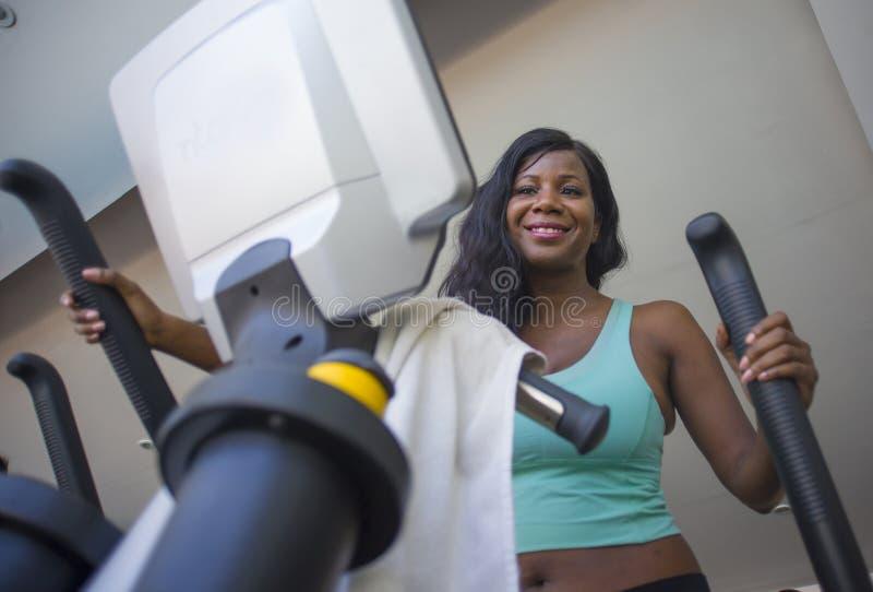 Binnen gymnastiekportret van jonge aantrekkelijke en gelukkige zwarte afro Amerikaanse vrouw die elliptische machinetraining ople stock afbeeldingen