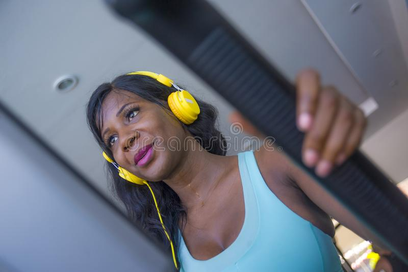 Binnen gymnastiekportret van jonge aantrekkelijke gelukkige zwarte afro Amerikaanse vrouw die met hoofdtelefoons elliptische mach stock fotografie