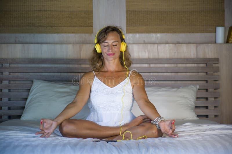 Binnen portret van mooie en geschikte gezonde vrouwenjaren '30 die yoga uitoefenen die aan muziek met hoofdtelefoons in bed stell stock foto