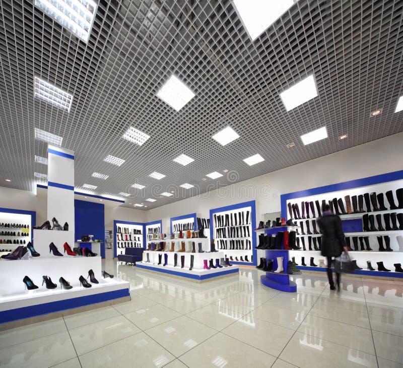 Binnen ruime schoenenwinkel met modellen op planken