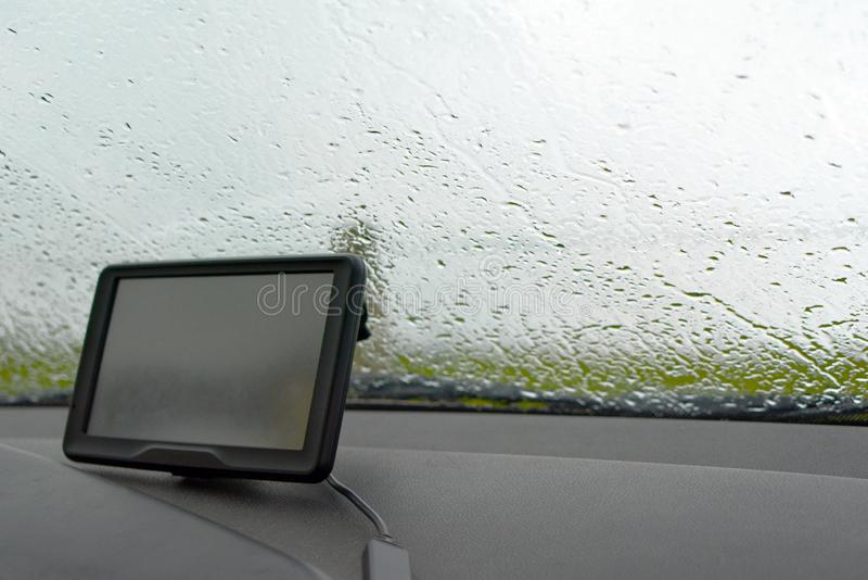 Binnen van een auto met regen op windschermvenster en GPS-navigatiesysteem in slecht weer royalty-vrije stock afbeelding