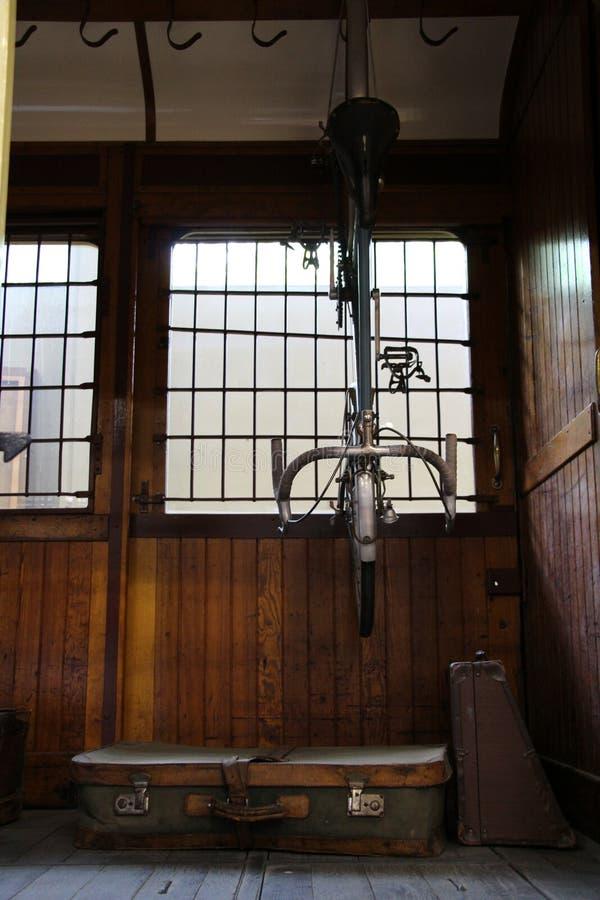 Binnen van een rustieke die ruimte met een fiets voor een venster van het plaatglas wordt opgeschort stock afbeelding