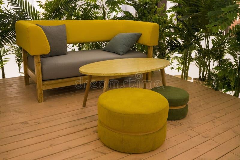 Binnenhuisarchitectuur, met zachte bank en gele houten lijst Comfortabele plaats voor rust stock foto