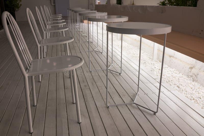 Binnenhuisarchitectuur, witte stoelen en cirkelbureaus, comfortabele plaats voor rust stock foto's