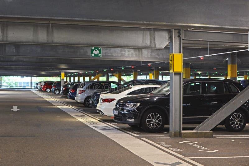 Binnenkant van donker vrij parkeerterrein die met meerdere verdiepingen tot winkelcentrum met geparkeerde auto's in Duitsland beh stock afbeeldingen