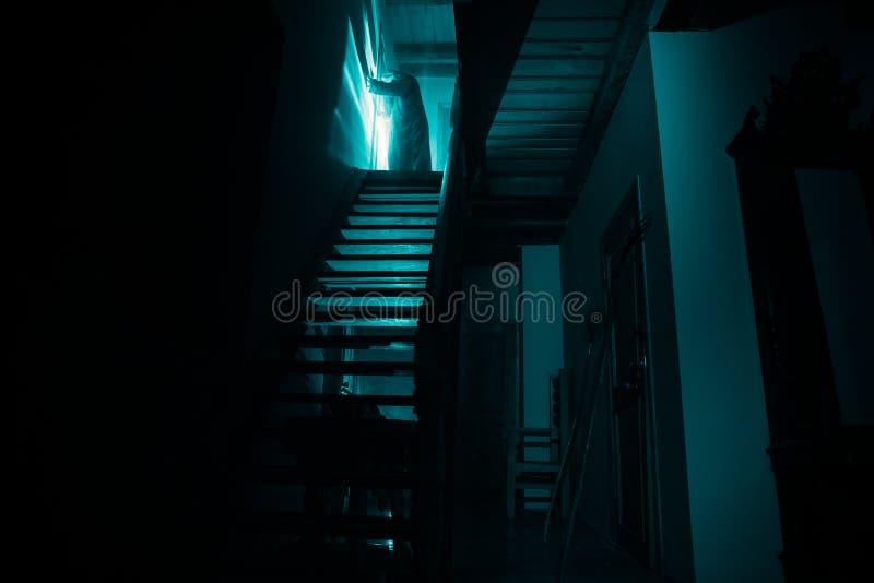 Binnenkant van oud griezelig verlaten herenhuis Silhouet die van verschrikkingsspook zich op kasteeltreden aan de kelderverdiepin stock foto's