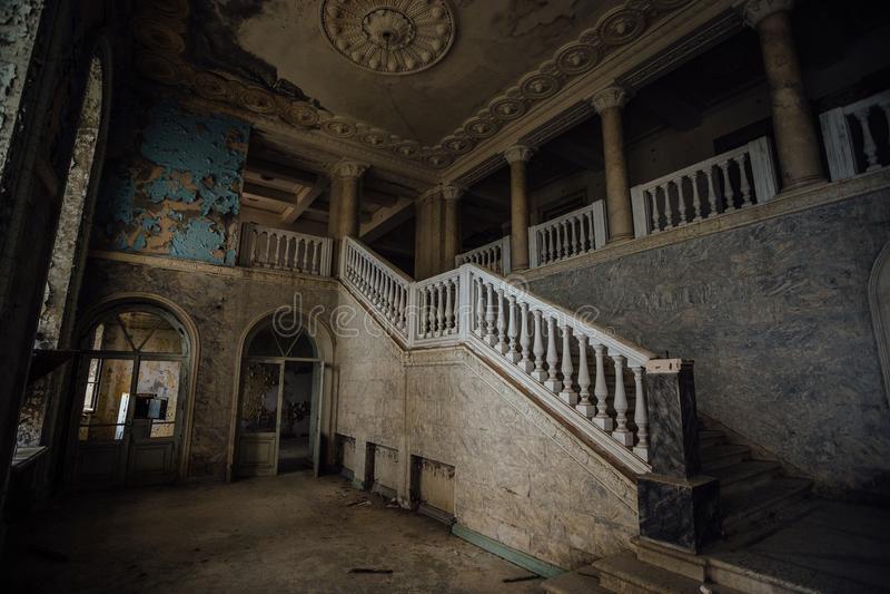 Binnenkant van oud griezelig verlaten herenhuis Trap en colonnade stock afbeeldingen