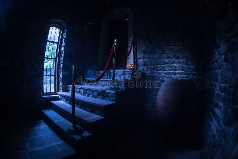 Binnenkant van oud griezelig verlaten herenhuis Trap en colonnade Halloween-pompoen op donkere kasteeltreden aan de kelderverdiep stock afbeelding