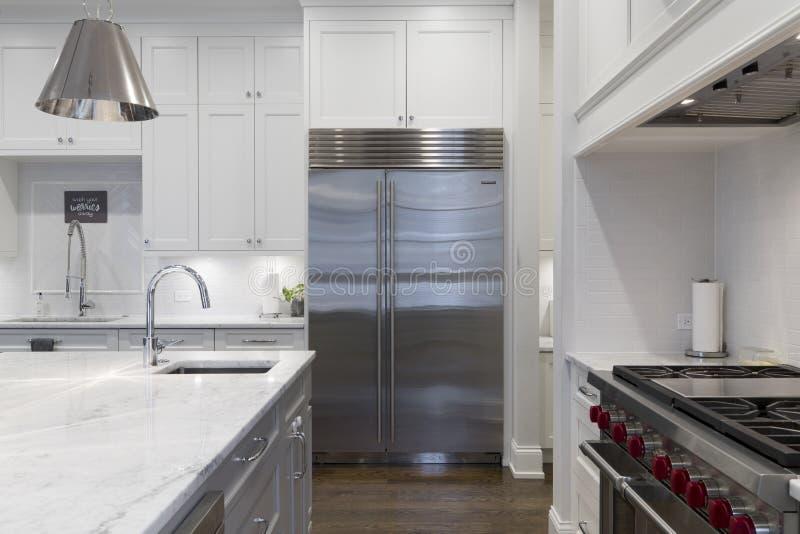 Binnenland dat van de moderne planken van de huiskeuken, laden, ijskast, oven, en een gootsteen wordt geschoten stock foto