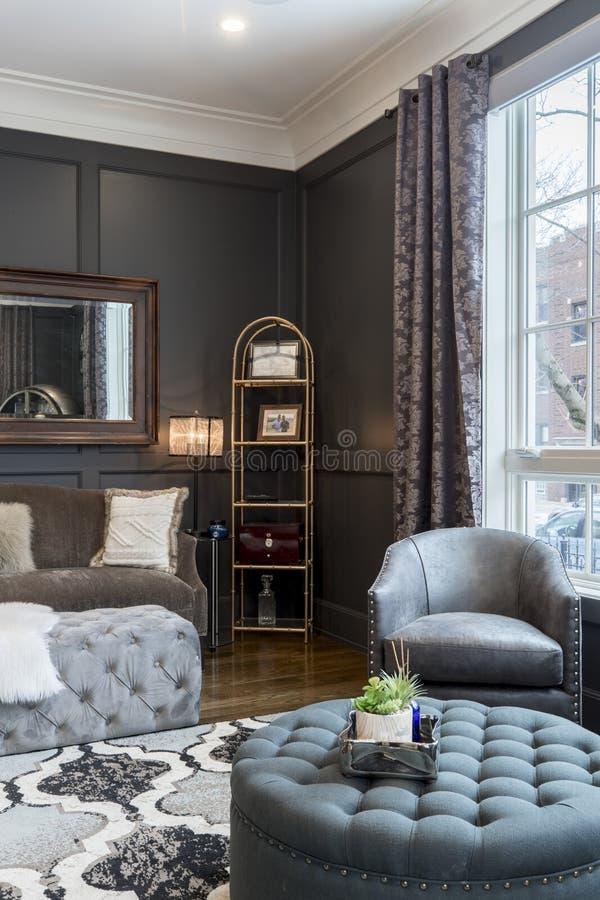 Binnenland dat van een luxueuze huiswoonkamer met leerleunstoelen en een ottomane met een plank wordt geschoten royalty-vrije stock afbeeldingen