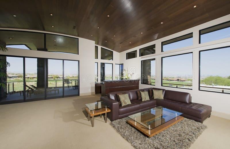 Binnenland met meubilair en grote vensters met buitenmeningen stock foto