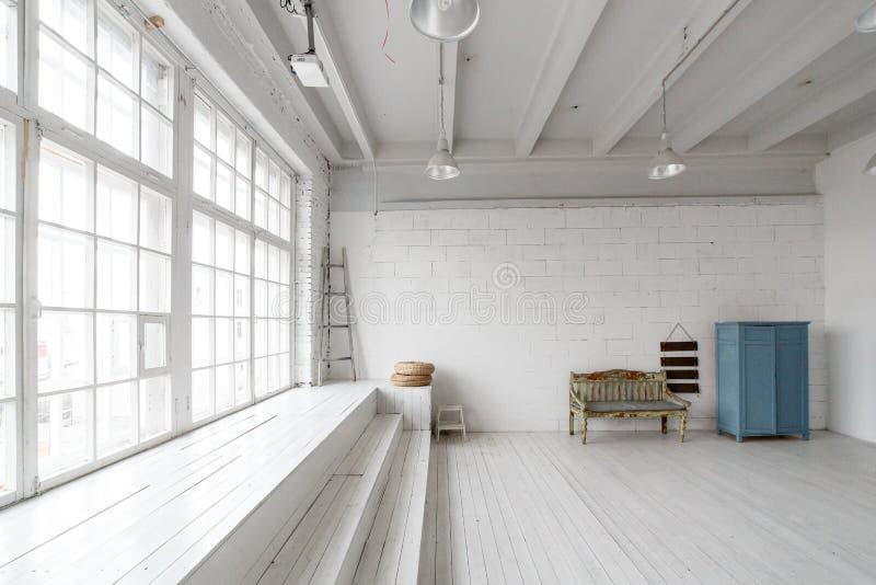 Binnenland met uitstekend meubilair, lichte studio met oude bank en blauw geval Ruime studio met een hoge plafond en a royalty-vrije stock afbeelding