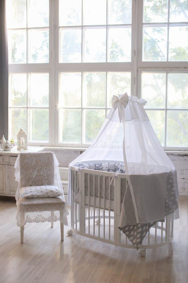 Binnenland van de kinderen` s ruimte, de stijl van de Provence, ovale babywieg, met luifel, licht binnenlands, groot mooi venster royalty-vrije stock foto