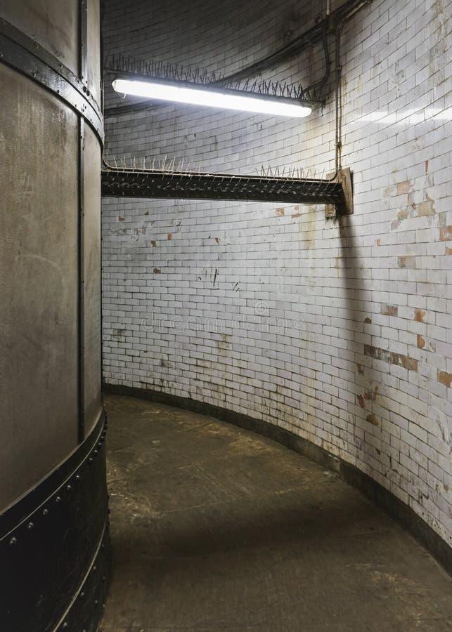 Binnenland van de voettunnel van Greenwich, vuile grungemuren en vloer in smalle die gang door neonlicht wordt aangestoken stock foto's