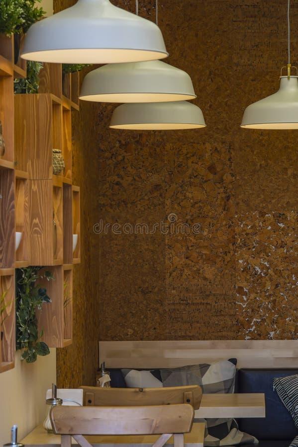 Binnenland van een modern restaurant met lijsten, houten meubilair, lampen en installaties royalty-vrije stock foto's