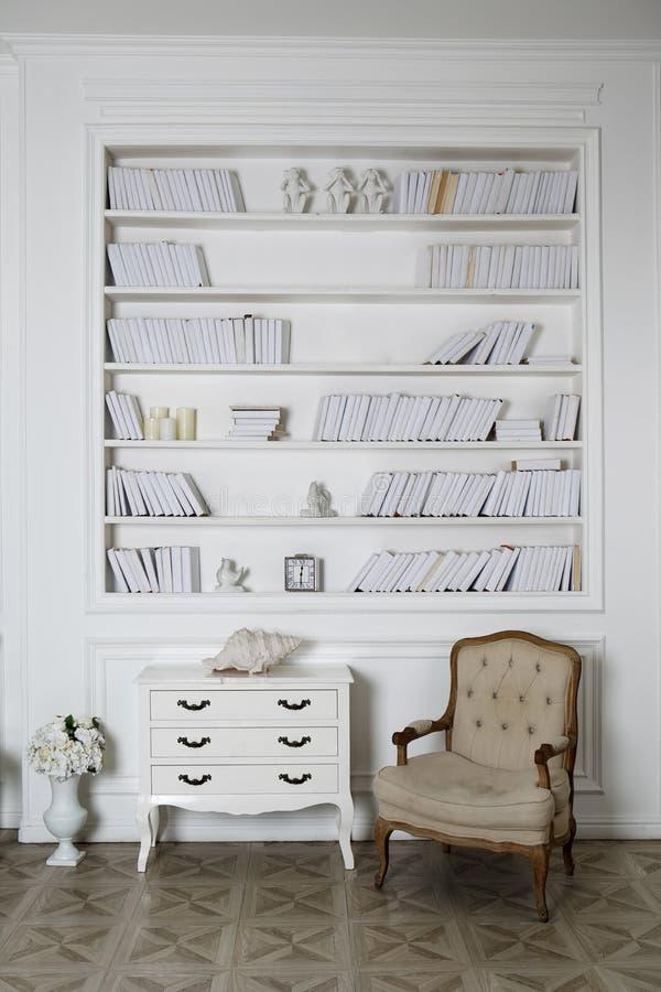 Binnenland van hite roomwith boekenrekken, leunstoel en een ladenkast royalty-vrije stock afbeeldingen