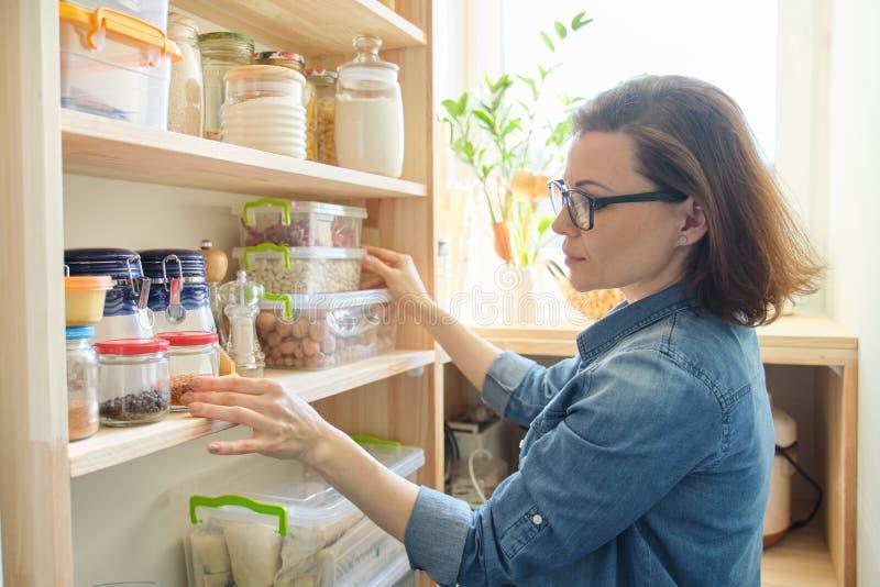 Binnenland van houten voorraadkast met producten voor het koken Volwassen vrouw die keukengerei en voedsel van de planken nemen royalty-vrije stock fotografie