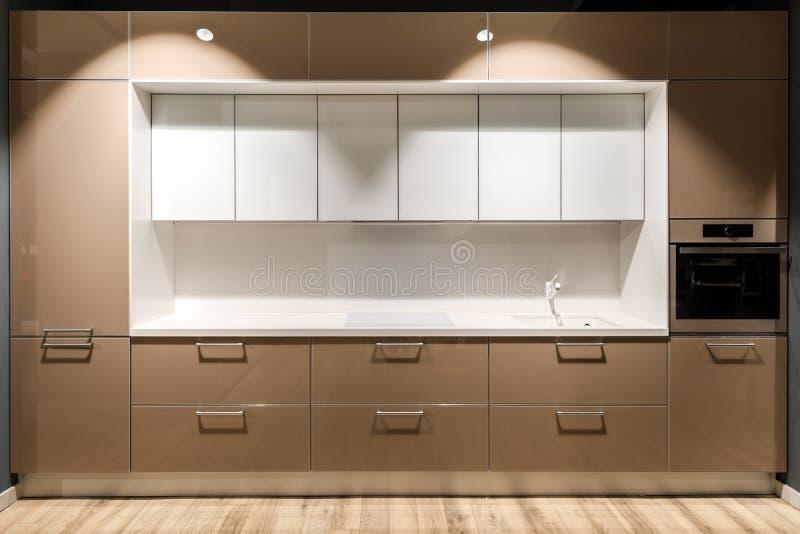 Binnenland van moderne keuken met modieus ontwerp in bruine en witte kleuren stock afbeelding