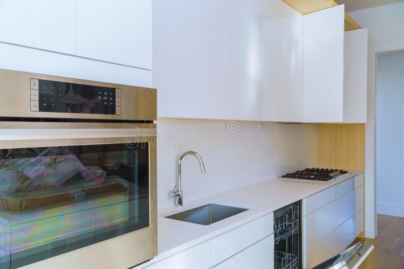 Binnenland van moderne keuken met toestellen op fornuis hoogste, marmeren teller met keuken witte kabinetten royalty-vrije stock foto's