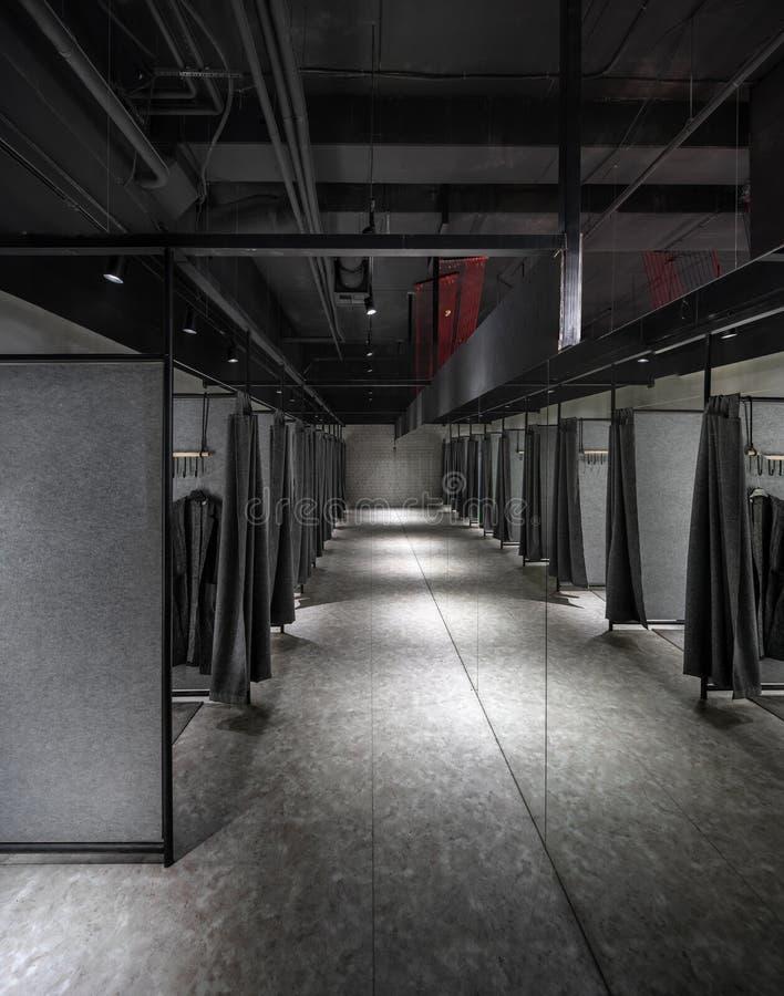 Binnenland van moderne klerenwinkel met montageruimte stock foto