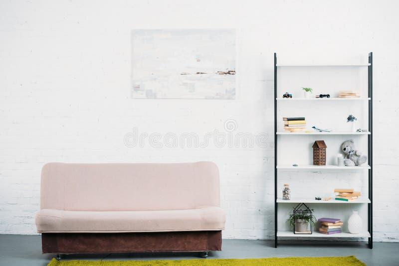 binnenland van moderne lichte woonkamer met laag en boekenrekken stock afbeeldingen