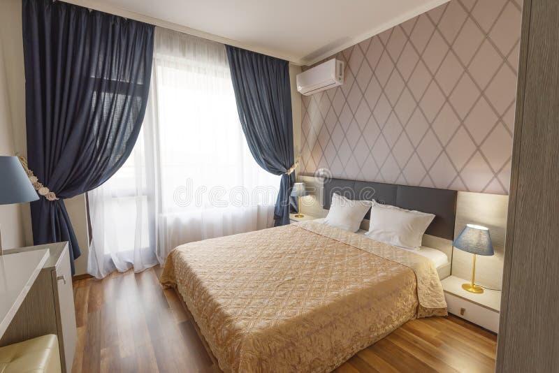 Binnenland van moderne slaapkamer met comfortabel tweepersoonsbed De vensters met lange gordijnen, gordijn en wijkt af Binnenland stock afbeelding
