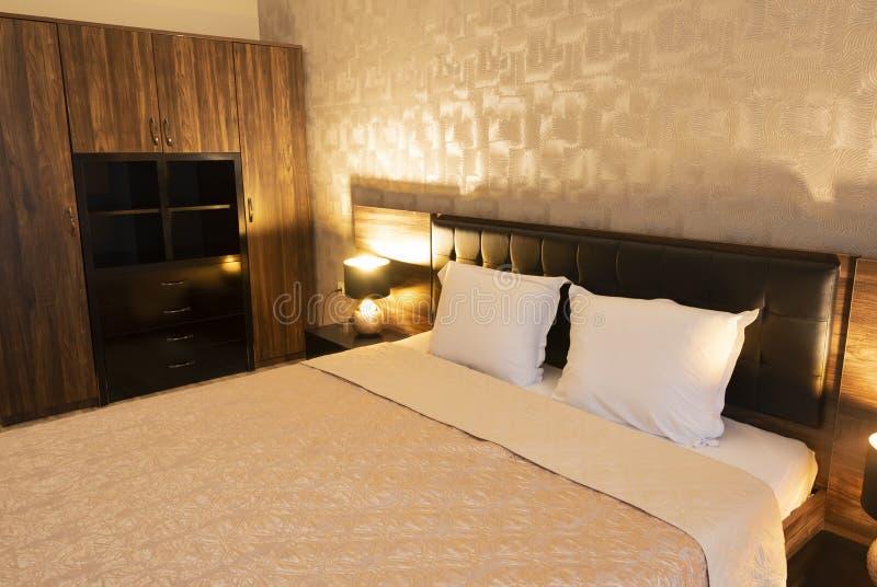 Binnenland van moderne slaapkamer met comfortabel tweepersoonsbed, wordrobe royalty-vrije stock foto