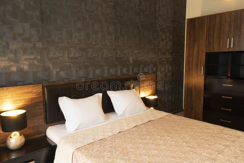 Binnenland van moderne slaapkamer met comfortabel tweepersoonsbed, wordrobe royalty-vrije stock afbeelding