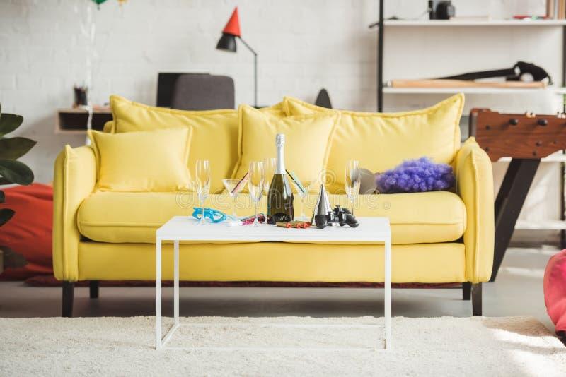 binnenland van moderne verfraaide woonkamer met champagnefles, glazen, bedieningshendel en partijlevering stock afbeelding