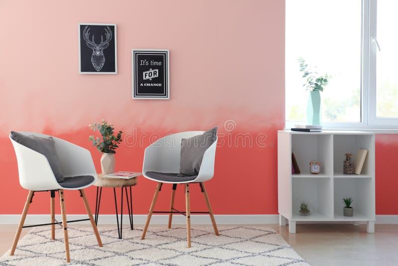 Binnenland van ruimte met comfortabele leunstoelen dichtbij roze muur royalty-vrije stock foto